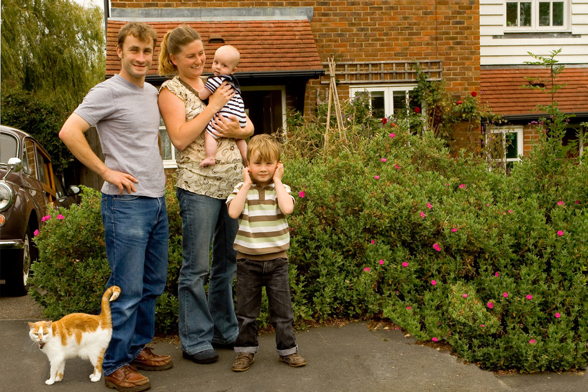 Family of parents and two sons outside their new family home - with their cat.